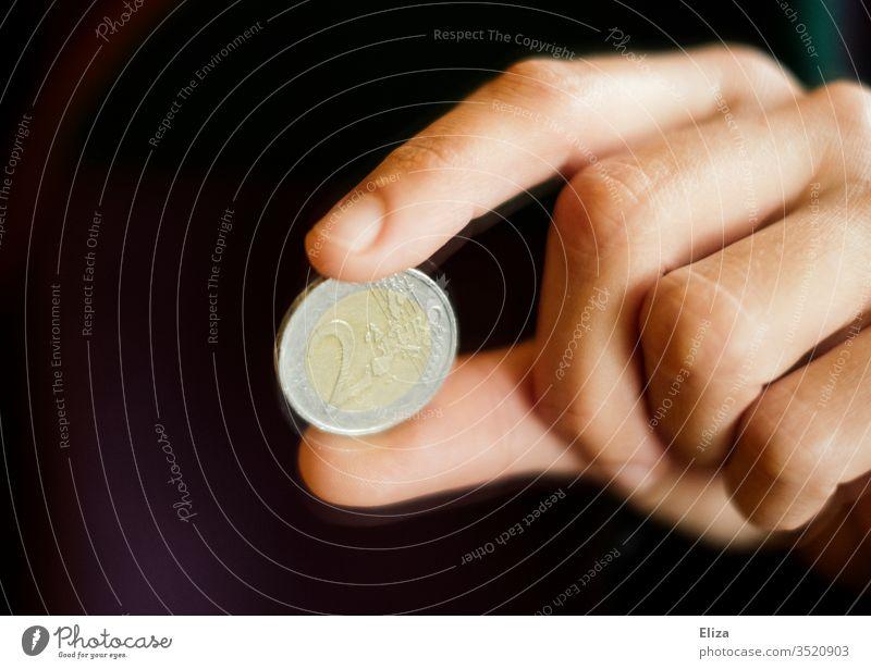 Eine Hand hält eine Zwei Euro Münze zwischen zwei Fingern Euromünze Geldmünze Bargeld Finanzen Trinkgeld Geldmünzen bezahlen schwarz dunkel sparen geben
