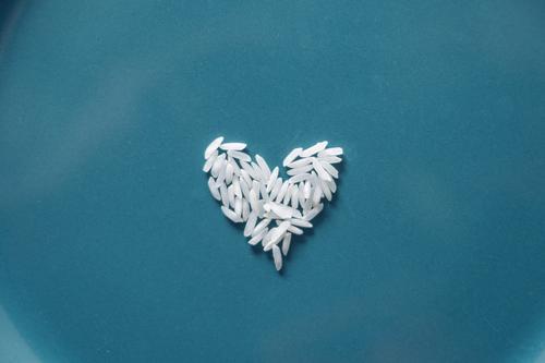 Ein weißes Herz aus Reiskörnern auf blauem Hintergrund Symbol Lebensmittel Nahrung Ernährung Kohlenhydrate Innenaufnahme Essen Hunger Welthunger Teller Diät
