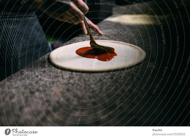 Pizzateig wird mit Tomatensauce bestrichen Pizzaiolo Pizza backen Handwerk kochen Essen diy Teigwaren Mantel Gastronomie Koch Mehl Handarbeit Mittagessen