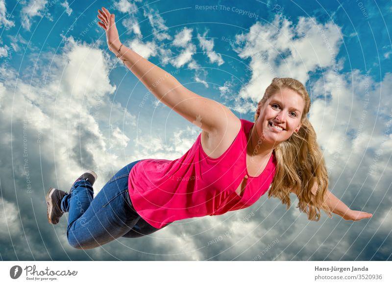 Junges Mädchen fliegt lachend hoch in Wolken frau himmel springen freudig jung blau sommer spaß fröhlichkeit freude freiheit leute kind ausserhalb energie aktiv