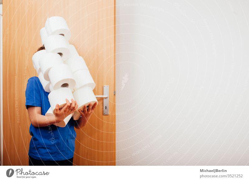 Junge bringt einen Stapel Toilettenpapier ins Zimmer übrig Kind Korona covid-19 Seuche Hamsterer Hamsterkauf heimwärts Ausbruch Pandemie Menschen Person privat