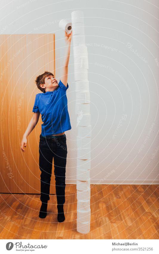Junge balanciert Toilettenpapierstapel übrig Stapel Gleichgewicht Langeweile Herausforderung Kind Korona covid-19 Seuche Spiel hoch Hamsterer Hamsterkauf