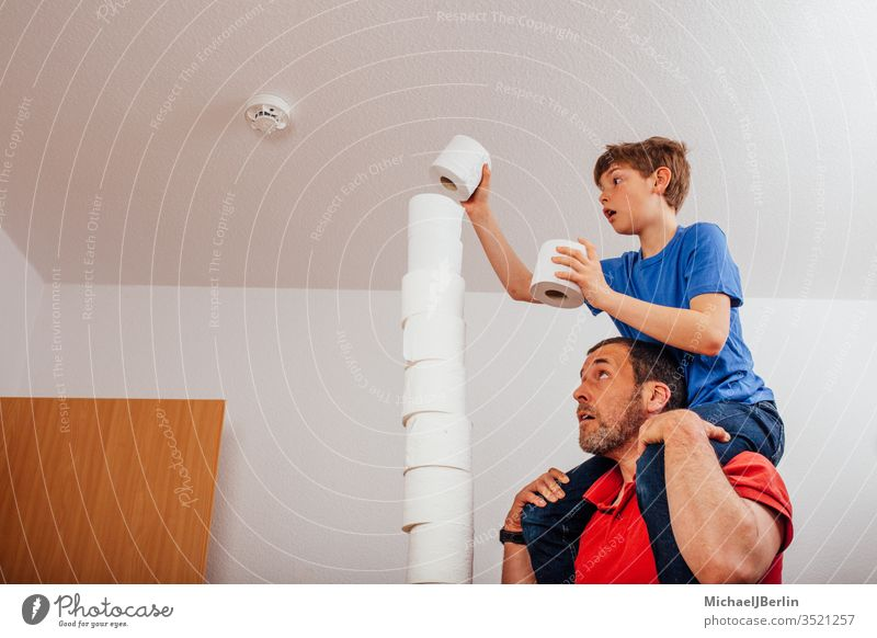 Vater und Sohn balancieren Toilettenpapierstapel übrig Stapel Gleichgewicht Langeweile Junge Herausforderung Kind Korona covid-19 Seuche Familie Spiel hoch