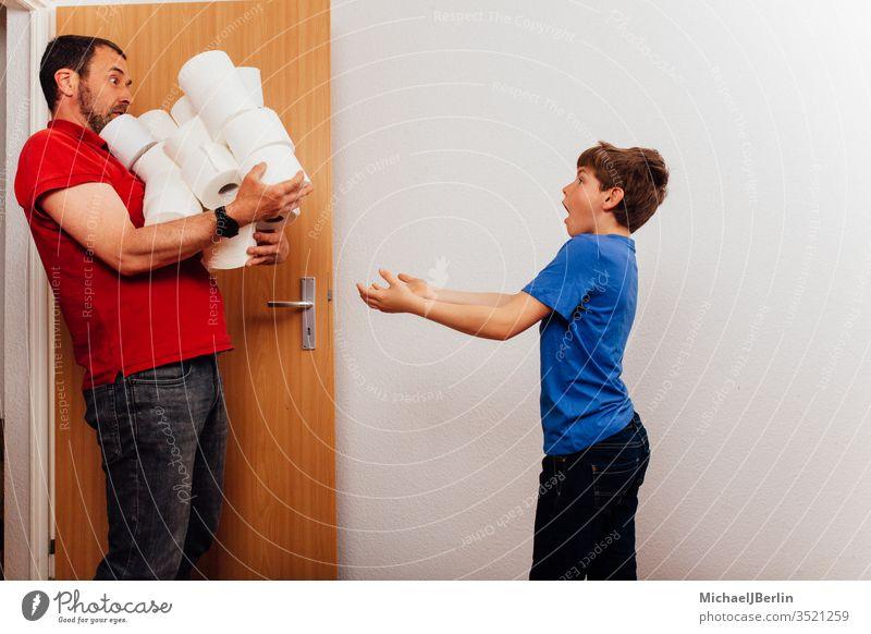 Vater bringt einen Stapel Toilettenpapier während des Ausbruchs der Coronavirus-Pandemie nach Hause übrig Junge Kind Korona covid-19 Seuche Familie Hamsterer