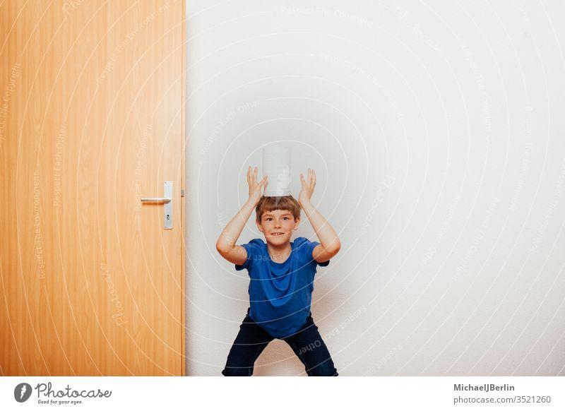 Junge balanciert Toilettenpapier auf dem Kopf übrig Gleichgewicht Kind Korona covid-19 Seuche Spaß Spiel Hamsterer Hamsterkauf heimwärts Ausbruch Pandemie