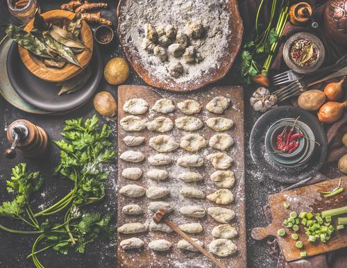 Hausgemachte Gnocchi bei der Zubereitung. Kartoffelteig auf dunklem, rustikalem Küchentisch mit Schneidebrett und gesunden Zutaten. Schmackhafte Hausmannskost. Ansicht von oben. Stilleben