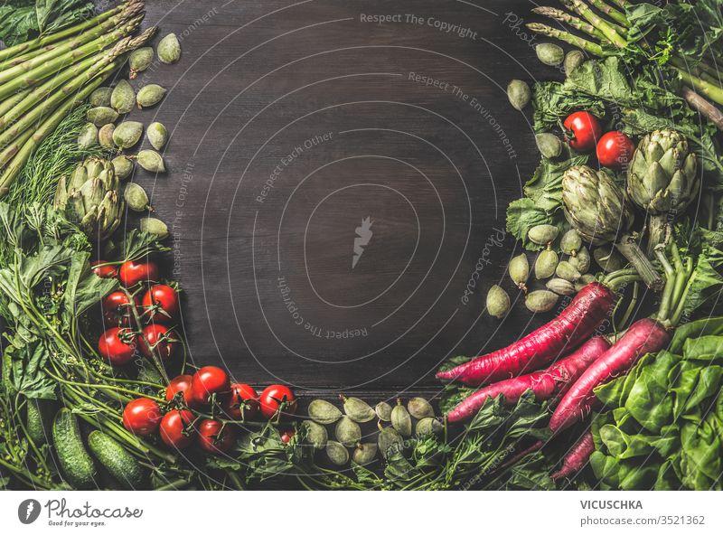 Lebensmittelhintergrund mit einer Gruppe verschiedener frischer Bio-Gemüsesorten aus dem Garten auf dunklem, rustikalem Holzgrund. Ansicht von oben. Gesunde, saubere vegetarische Zutaten: Tomate, Kopfsalat, Wurzelgemüse, Artischocken