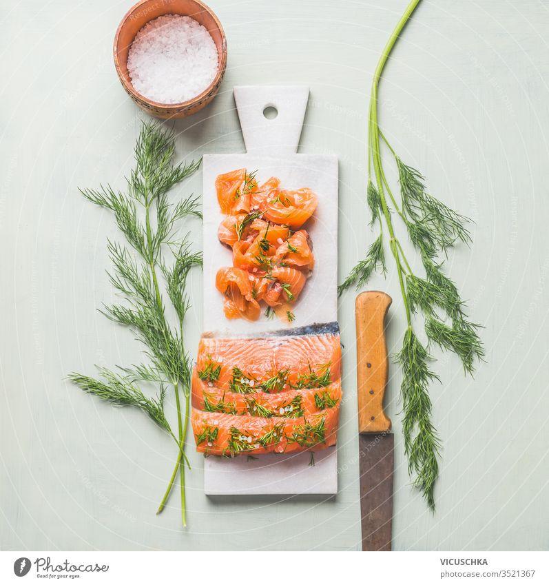 Hausgemachtes geräuchertes Lachsfilet mit Dill und Zitrone auf Marmorschneidebrett serviert selbstgemacht Filet Murmel Schneidebrett Licht Hintergrund