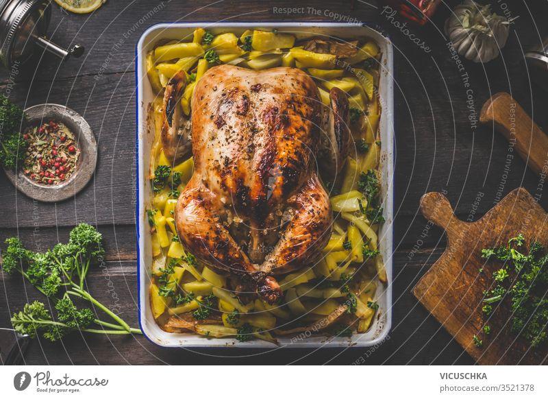 Köstlich gebratenes ganzes Huhn oder Truthahn mit Kartoffeln auf dunklem, rustikalem Holzküchentisch mit Kräutern und Gewürzen. Ansicht von oben. Hausmannskost