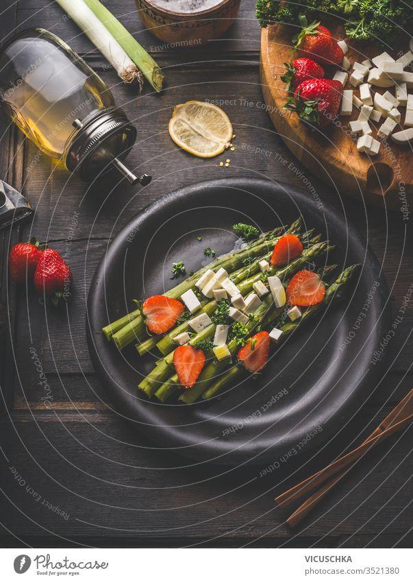 Schmackhafter Spargelsalat, belegt mit Erdbeeren und Frischkäsewürfeln, serviert in schwarzer Platte auf dunklem, rustikalem Tischhintergrund mit Zutaten. Ansicht von oben. Gesundes Essen. Hausmannskost und Essen