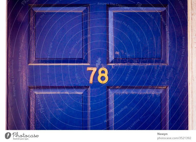Hausnummer 78 an einer dunkelblau verwitterten und abgenutzten hölzernen Haustür 78 Zahl Adresse britannien klassisch stilvoll abschließen Nahaufnahme