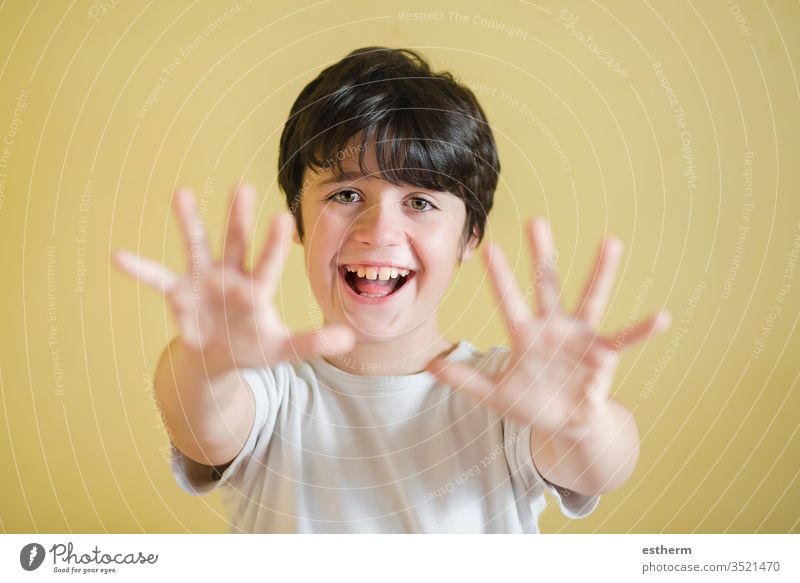 Glückliches Kind streckt die Hände hoch, Hintergrund verschwommen sich ausbreiten zeigend Lächeln Freude Zeichen Euphorie euphorisch schreien heiter Energie