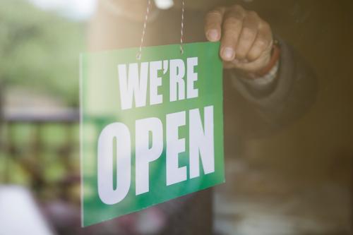 Geschäftsinhaber hängt ein offenes Schild an eine Glastür Werbung Transparente Bar Holzplatte Business beschäftigt Café Großstadt Konzept Tag Tür Eingang