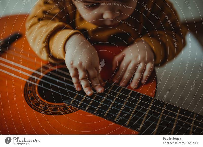 Gitarre spielendes Kind Spielen Fröhlichkeit Kaukasier im Innenbereich Neugier unschuldig Mädchen heimwärts Blick gemütlich Freude Lifestyle niedlich Kindheit