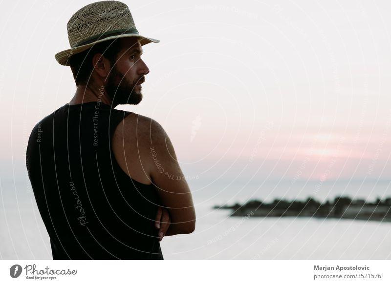 Junger Mann genießt Sonnenuntergang am Meer Erwachsener Abenteuer allein Strand Küste Morgendämmerung Abenddämmerung genießen Genuss Freiheit Typ gutaussehend