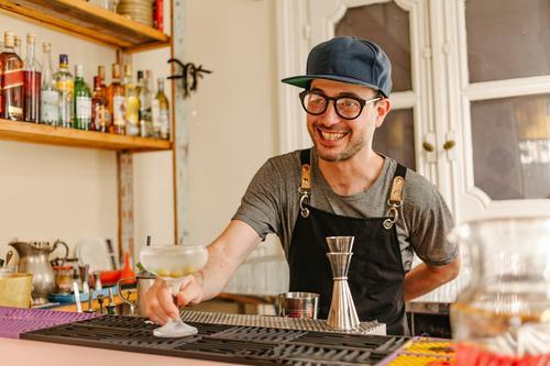 Kellner zeigt ein eiskaltes Glas mit einem an der Bar einer modernen Bar zubereiteten Cocktail zeigen dienen Alkohol Lächeln transferieren liquide Brille Minze
