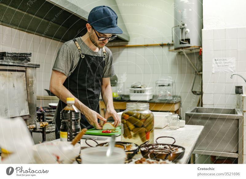 Mann mit Brille und Mütze kocht in einer Restaurantküche mit Töpfen mit Essen, Öl und Pfannen wirtschaftlich Container Urelemente professionell rostfrei Geräte