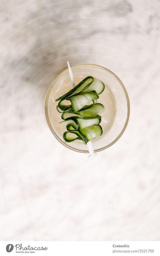 Teller mit einem Gurkenspieß auf weißem Hintergrund vertikal Antenne Gemüse Salatgurke Spieß Genuss Lebensmittel Lebensstile reich verdrehen Cocktail filigran