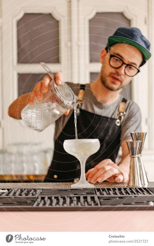 Vertikales Foto eines Kellners, der Flüssigkeit in ein Glas mit Eis in ein Frost-Cocktailglas umfüllt transferieren liquide Alkohol Bar Gießen Brille Minze