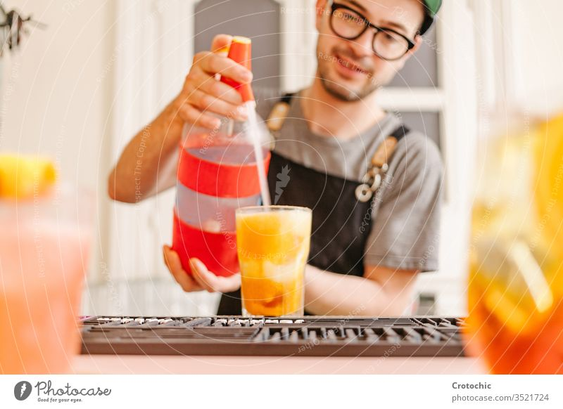 Kellner mit Schürze, Gläsern und Kappe, der an einer Bar Soda in ein Glas mit einem Cocktail wirft platschen mischen Flasche verabreicht Gießen Brille