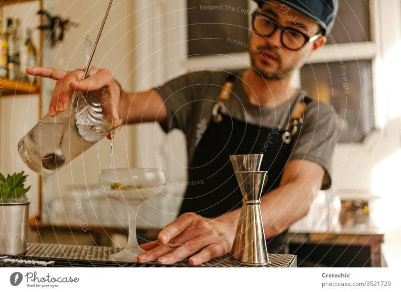 Kellner, der Flüssigkeit in ein Glas mit Eis in ein Frost-Cocktailglas umfüllt transferieren liquide Alkohol Bar Gießen Brille Minze Schürze Hotel frisch