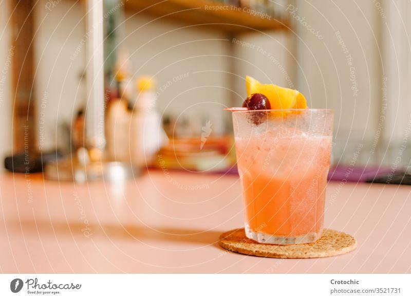 Kristallglas mit einem eisgekühlten Cocktail mit einem Stück Orange und einer Kirsche vertikal trinken Alkohol cool Eis Frische orange dunkel Getränk Eleganz