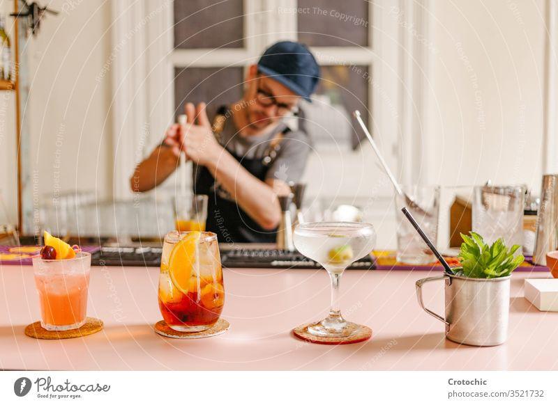 Selektiver Fokus in drei Cocktailgläsern, zubereitet mit einer Metalltasse mit Minze am Rand an einer Bar Kulisse roh Varieté selektiv dienen Alkohol modern