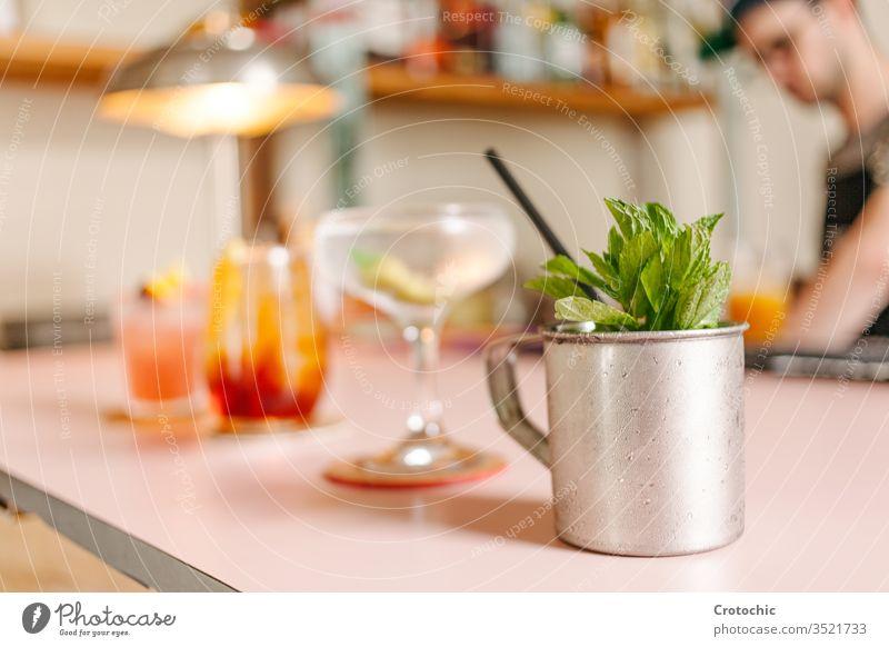 Selektive Konzentration auf einen Metallbecher mit Minze und drei Cocktailgläser, die daneben auf einer Bar zubereitet werden metallisch Empfänger Kulisse roh