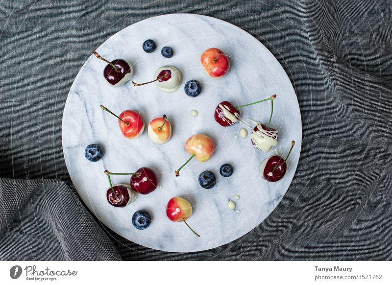 Orangen und rote Kirschen mit Beeren Frucht Sommer frisch lecker saftig Natur Ernte Orangenkirsche weiße Schokolade Blaubeeren organisch Lebensmittel grün