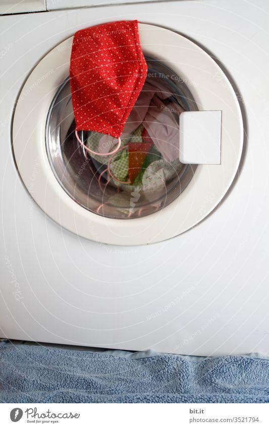 Rote selbstgenähte Schutzmaske aus Stoff mit Punkten, hängt vor der Wäsche, Desinfektion auf der Tür der Waschmaschine im Bad. Steriler Mundschutz zum Schutz vor einer Ansteckung mit Corona, Viren, Grippe, Krankheiten und gegen Smog, Luftverschmutzung.