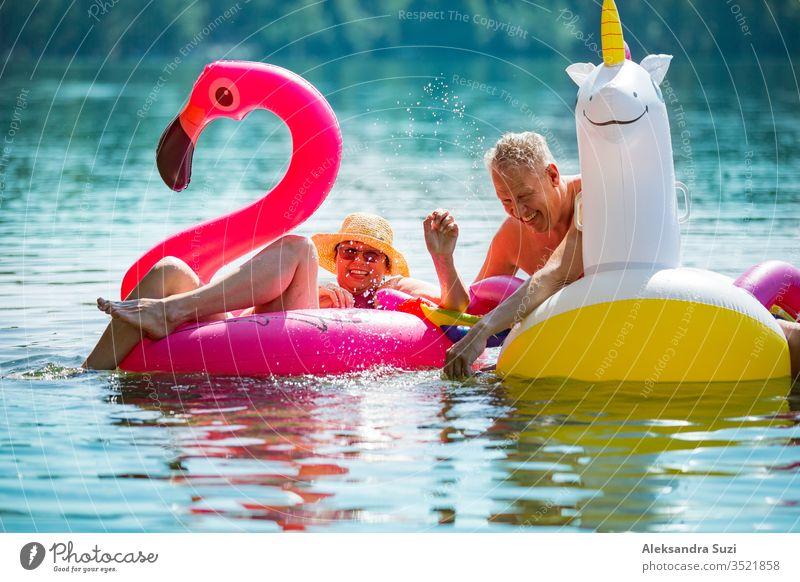 Älteres Paar amüsiert sich auf aufblasbaren Flamingos und Einhörnern. Lustige aktive Rentner, die zusammen glücklich den Sommerurlaub am Strand in Europa genießen, lachen, den Narren spielen, Wasser spritzen.