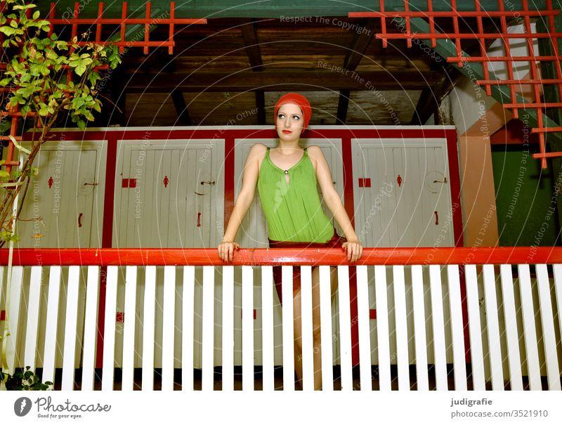 Das Mädchen mit der schönen roten Badekappe und grünem Badeanzug stützt sich auf das Geländer der Damenumkleide. Eine Sommerliebe. Frau Badebekleidung Badehaube