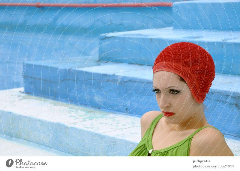 Das Mädchen mit der schönen roten Badekappe und grünem Badeanzug sitzt auf der Treppe des leeren Nichtschwimmerbeckens. Eine Sommerliebe. Frau Badebekleidung