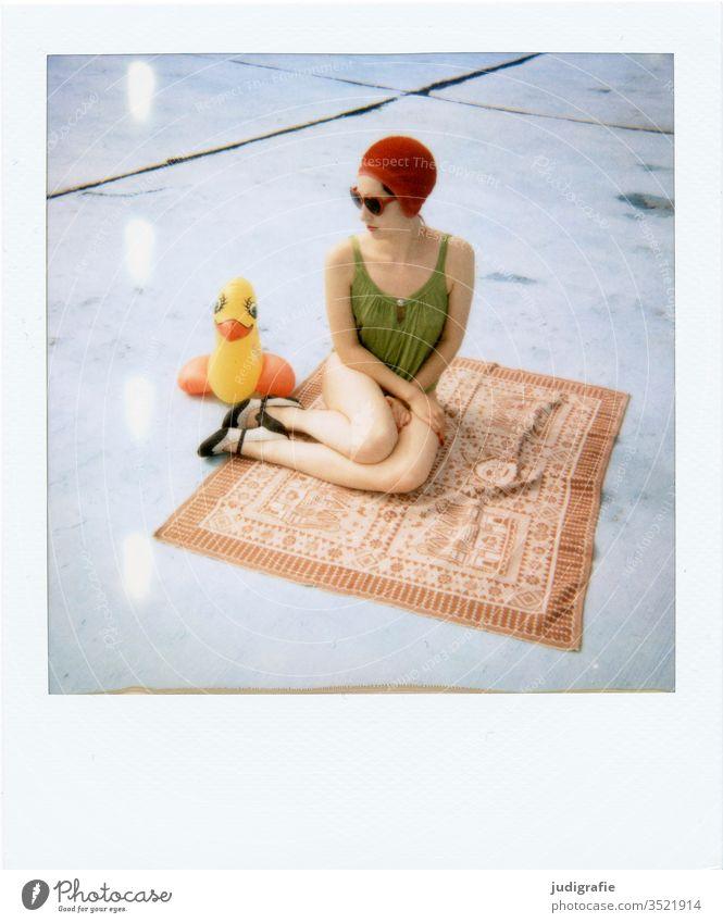 Das Mädchen mit der schönen roten Badekappe und grünem Badeanzug sitzt mit ihrer Gummiente auf einer Decke. Eine Sommerliebe. Frau Badebekleidung Badehaube Haut