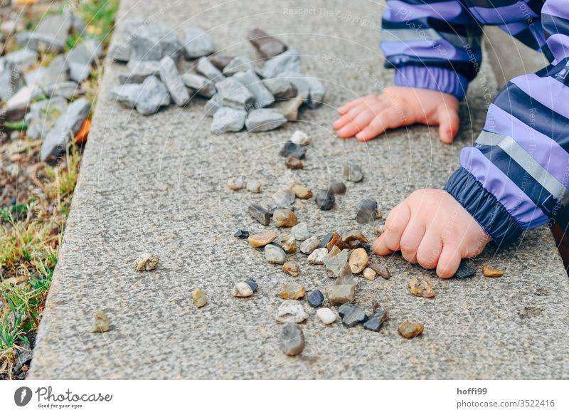 Kinderhände sortieren kleine Steine auf einer Mauer Kinderhand Spielen Hand Kindheit Kleinkind Farbfoto Finger 1-3 Jahre Detailaufnahme 3-8 Jahre Freude