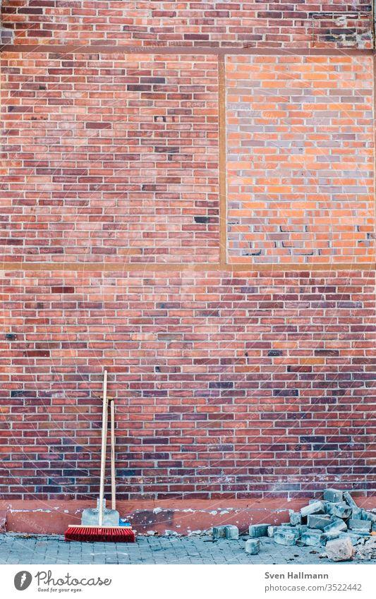 Besen und Schaufel stehen an Ziegelwand Tag Reinigen Außenaufnahme Wand Kehren Menschenleer Sauberkeit Farbfoto dreckig Besenstiel Mauer Detailaufnahme Bauwerk