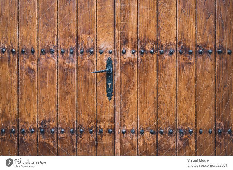 Traditionelle Holztür mit Eisennägeln verziert Tür abstrakt Hintergrund Textur strukturell geknackt geschält im Freien Außenseite Farbe Detailaufnahme künstlich
