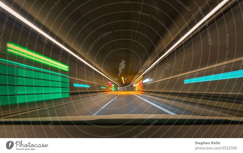 Schnelle Fahrt mit meinem Auto durch einen Tunnel mit Führungsleinen und Lichtern und Unschärfe-Effekt. abstrakt Alkohol Kunstlicht Asphalt Automobil