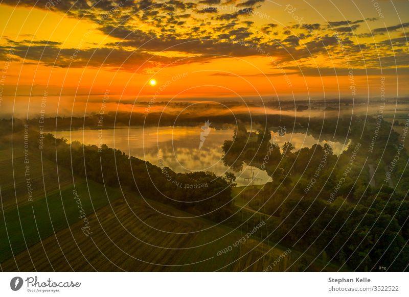 Herrlicher Sonnenaufgang über einem vernebelten See, orangene Farbgebung Aufgang Morgen Nebel ruhig Wasser Morgendämmerung Himmel Natur Reflexion & Spiegelung
