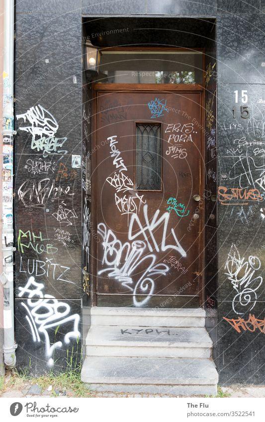 Haustür mit Graffitis Tür Eingang Treppe Hausfront verschmiert grau schwarz braun Holz alt Granit Unkraut Tags weiß Schmiererei Verfall Menschenleer Wand