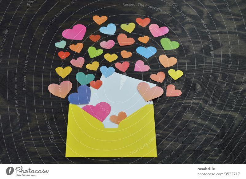 gelber Briefumschlag geöffnet mit leerer weißer Karte zum selbst Beschriften, viele bunte aus Papier ausgeschnittene Herzchen die daraus hervorkommen als lieber Gruß aus der Ferne bei sozialer Distanz z.B. zum Muttertag oder Geburtstag auf schwarzem Holz