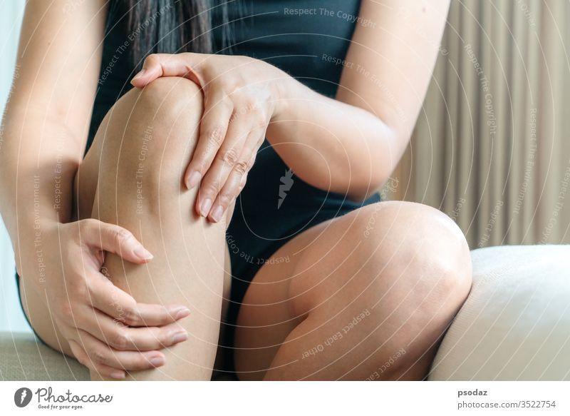 Frauen Knie schmerzhaft, Frauen berühren das schmerzhafte Knie zu Hause Unfall Schmerzen Fußknöchel Arthritis Asien Athlet Schönheit Körper Knochen gebrochen