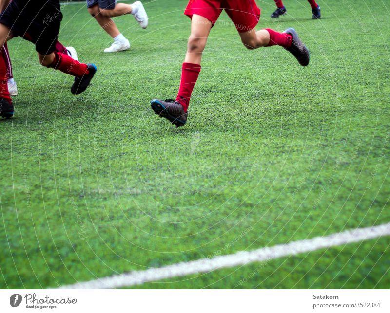 Die Fussballer treten in farbigen Sportarten der Grundschule an Fußball Kinder Schule Spiel grün Streichholz spielen Junge jung Hintergrund Feld Spieler