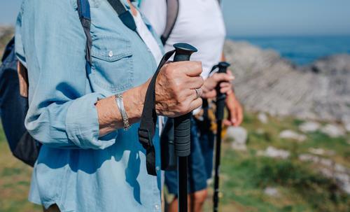 Älteres Ehepaar übt Trekking im Freien unkenntlich Senior Paar Trekkingstöcke wandern Berge u. Gebirge Hände Detailaufnahme Landschaft Feld Natur alt