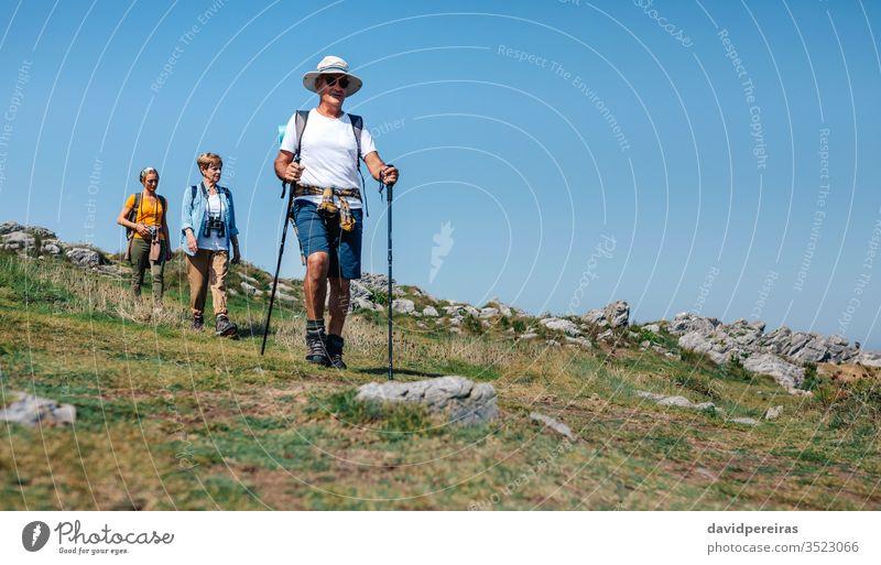 Drei Personen, die Trekking im Freien praktizieren Wanderer lokaler Tourismus Familie Landschaft laufen Trekkingstöcke Senior Natur Nordic Walking Sommer