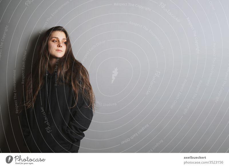 traurige junge Frau, die an einer Wand lehnt und in Kontemplation zur Seite schaut Mädchen gothic Denken Teenager Jugendzeit Traurigkeit Depression Melancholie