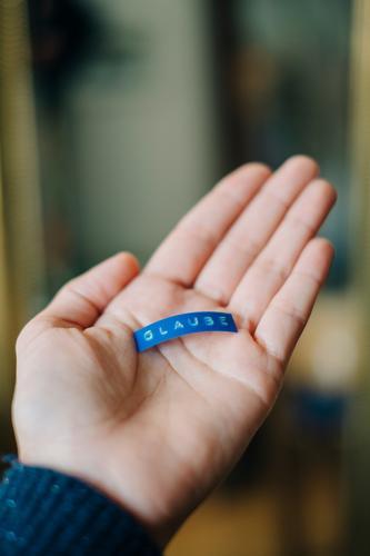 Eine Person die ein blaues Etikett mit dem Wort Glaube in der Hand hält. Konzept Religion und Vertrauen in Gott. gläubig Christentum geben missionieren Hoffnung