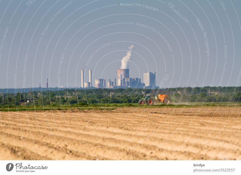 Braunkohlenkraftwerk Niederaußem, im Vordergrund ein Bauer welcher Pestizide auf sein Feld ausbringt. Braunkohlenverstromung und konventionelle Landwirtschaft ,verantwortlich für Klimawandel und Verseuchung der Umwelte
