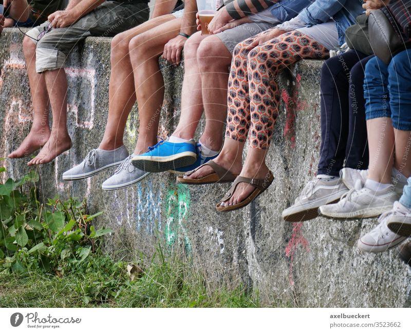 junge Leute chillen auf Mauer und lassen die Füße baumeln Beine sitzen viele Festival Barfuß jugend Sommer freizeit Freizeit & Hobby Fuß warten anonym