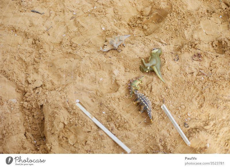 Spielzeug Dinosaurier in Sandkiste spielzeug kinderspiel sandkiste spielplatz Reptilien reptil Figur Spielfigur fantasie tyrannosaurus rex Stegosaurus Garten